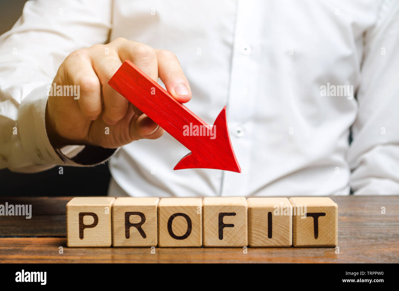 Businessman holds down arrow over word Profit. The concept of low profits in the company. Unprofitable business. Financial crisis. Capital outflow. Ba - Stock Image