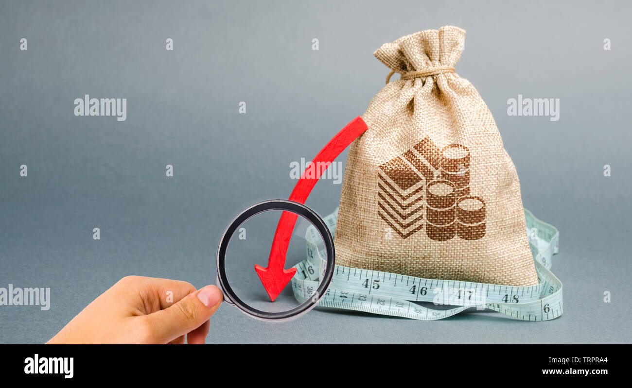 Money bag with red arrow down. The concept of reducing profits. Unprofitable business. Capital outflow. Report and financial performance. Limited budg - Stock Image