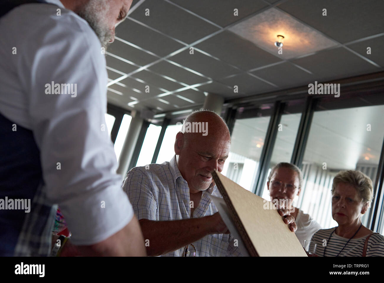 A group of elderly retired friends celebrating a 50th wedding anniversary at a restaurant with the happy couple unwrapping presents Stock Photo
