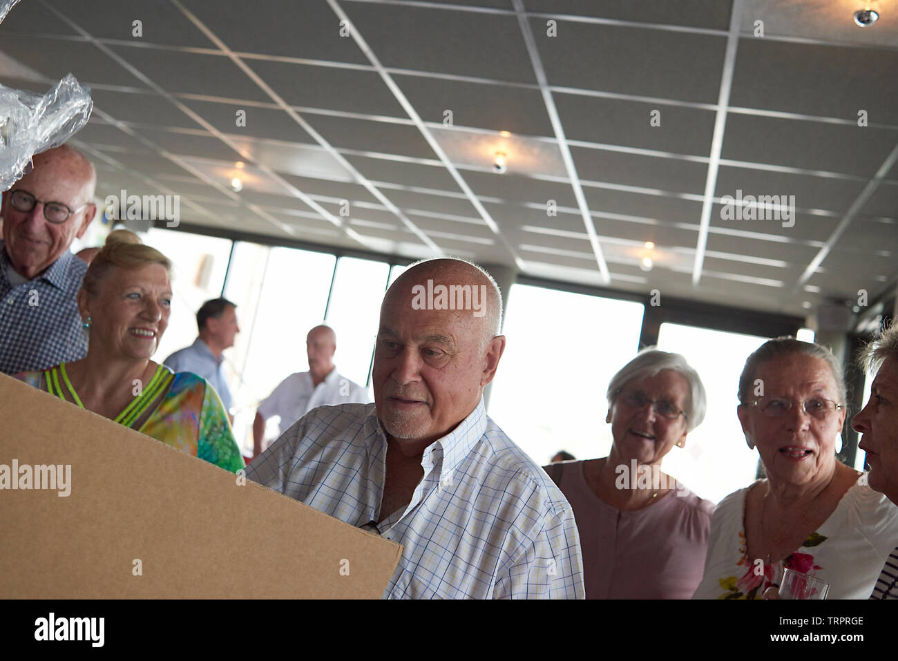 A group of elderly retired friends celebrating a 50th wedding anniversary at a restaurant with the happy couple unwrapping presents - Stock Image