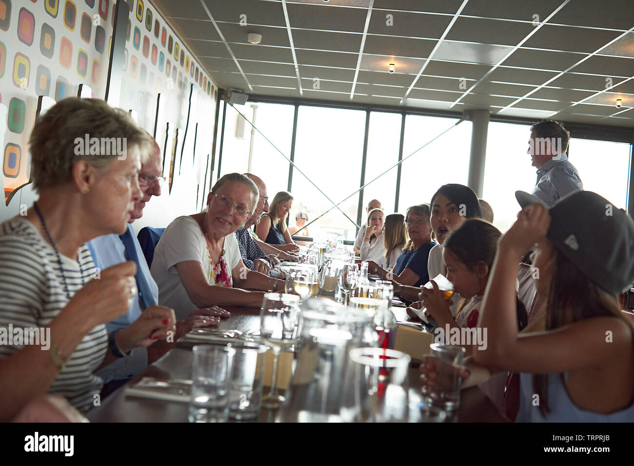 A group of elderly retired friends celebrating a 50th wedding anniversary at a restaurant with lots of laughter, speeches, presents, and joy - Stock Image