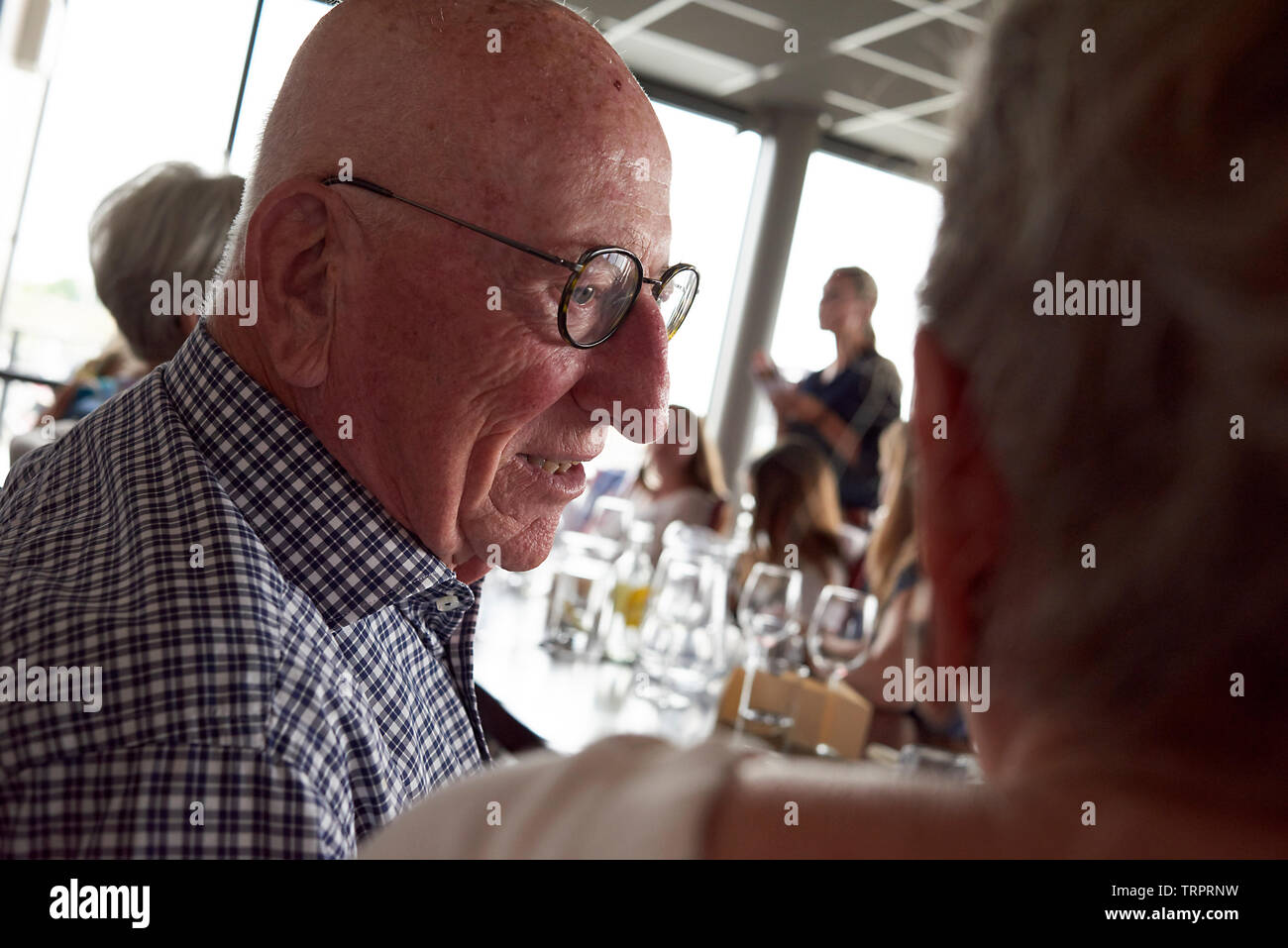 A group of elderly retired friends celebrating a 50th wedding anniversary at a restaurant with lots of laughter, speeches, presents, and joy Stock Photo
