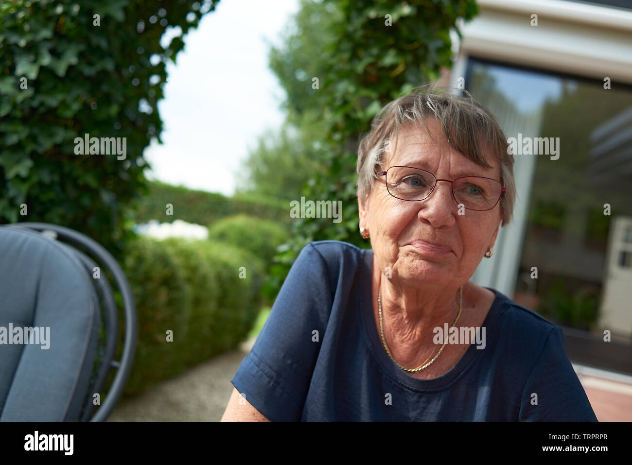 Healthy looking elderly woman sitting in her back garden looking happy and excited in summer sunshine - Stock Image