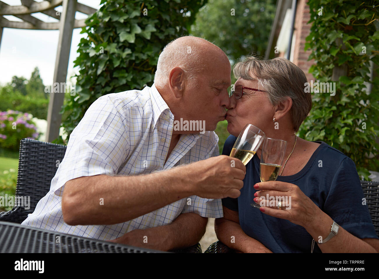 Healthy caucasian couple celebrating their 50th wedding anniversary with a kiss and a glass of champagne in their back garden in summer sunshine - Stock Image