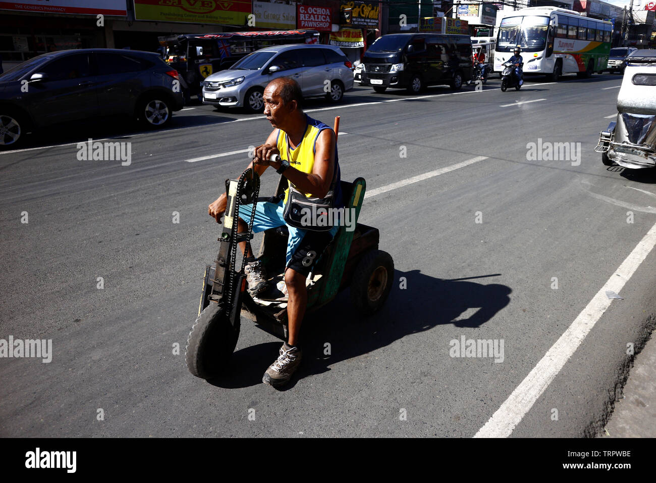 ANTIPOLO CITY, PHILIPPINES – JUNE 7, 2019: A person with disability peddles candies and cigarettes on his improvised wheelchair at a busy street. - Stock Image