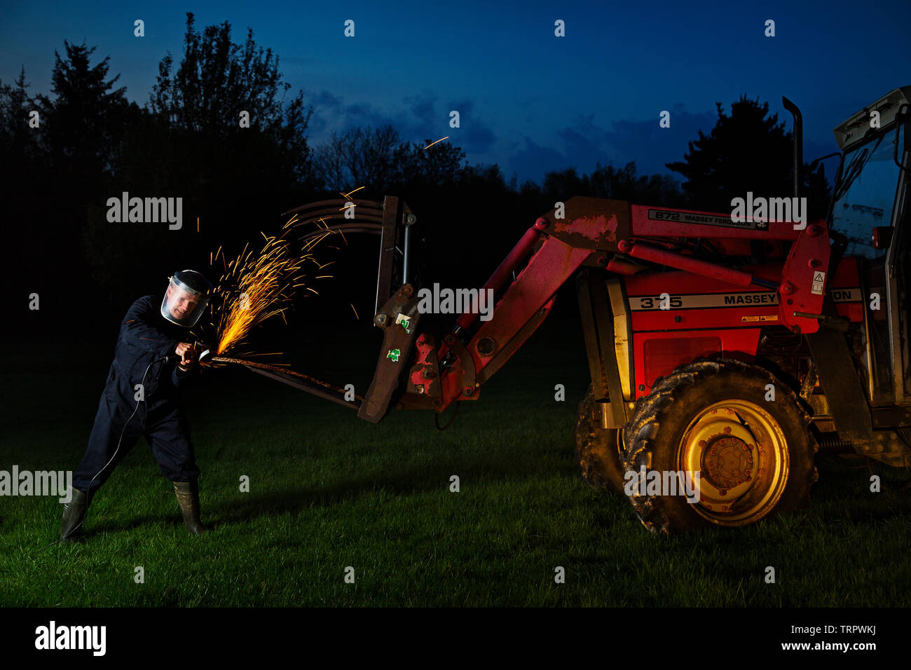 A farmer making repairs late into the night - Stock Image