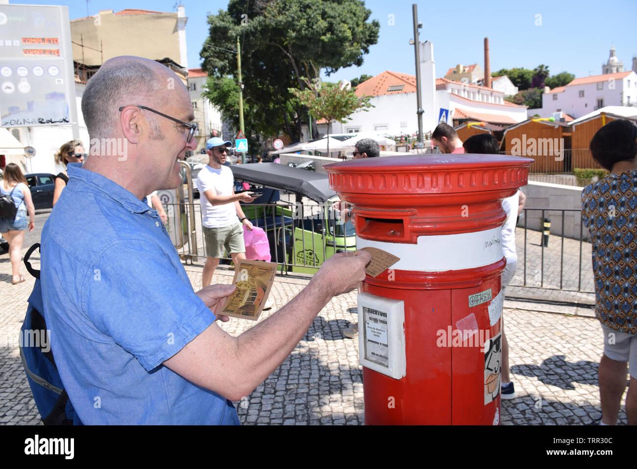 Tourist posting postcards, Largo das Portas do Sol, Lisbon, Portugal, June 2019 - Stock Image