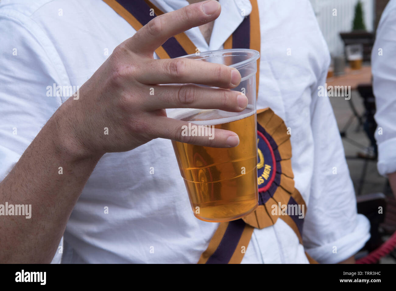 Pint of beer in a one use plastic cup Morris Dancers 2010s UK HOMER SYKES - Stock Image