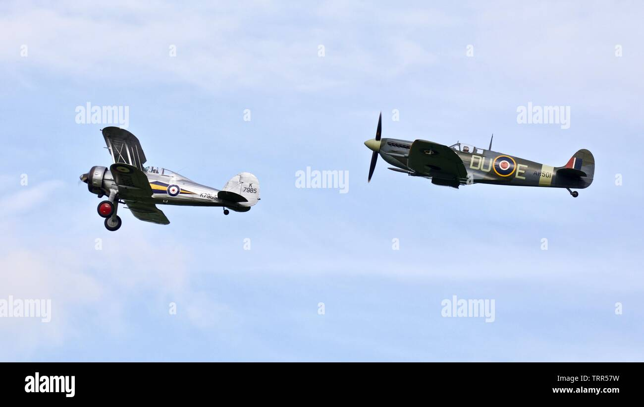 1941 Supermarine Spitfire (AR501) and a 1938 Gloster Gladiator (K7985) performing a unique flypast at the Shuttleworth Air Festival on the 2 June 2019 - Stock Image