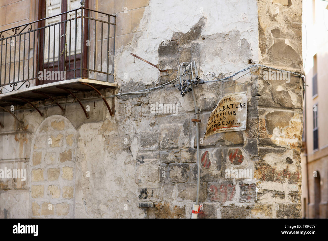 Detail of the corner of an old stone house with wiring and oldness of signboard in Palermo, Italy. Text: 'Welding work Electric and gas welding..' - Stock Image