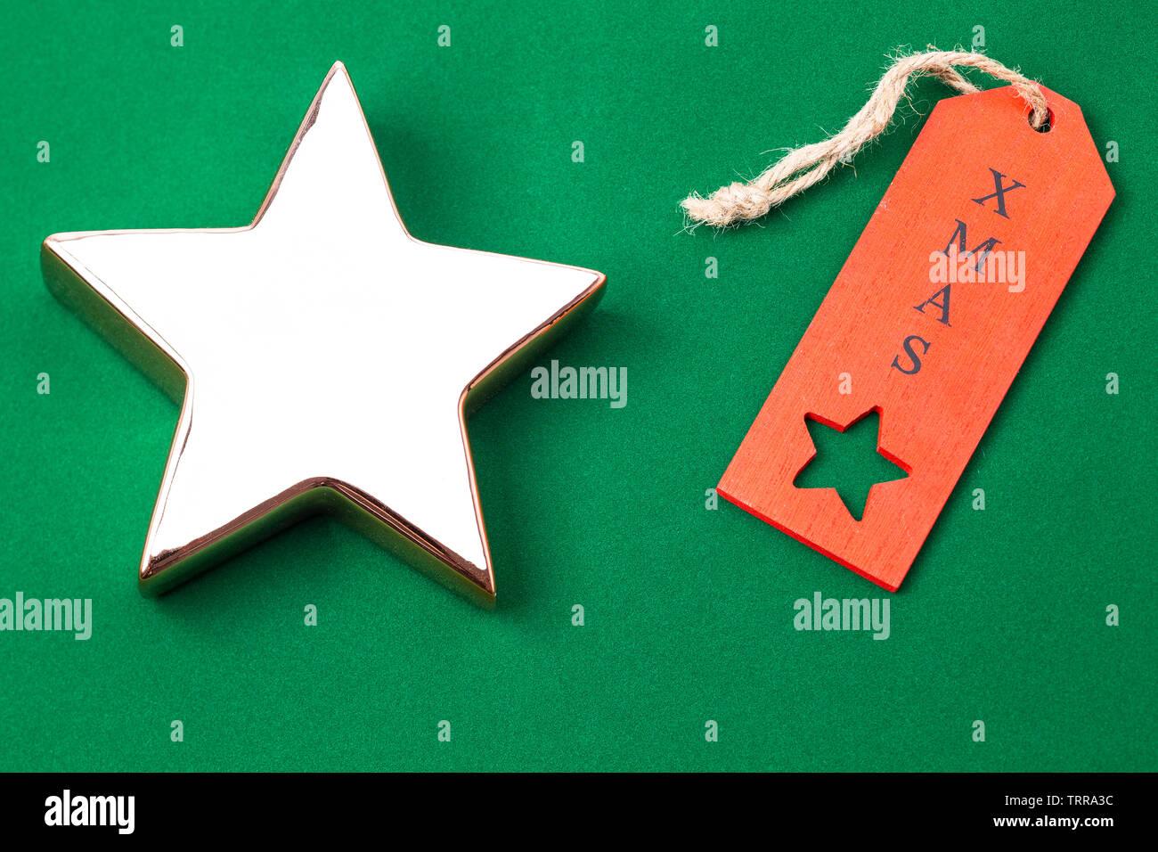 Das Foto zeigt einen goldenen Stern mit rotem Weihnachtsetikett isoliert auf grünen Hintergrund - Stock Image
