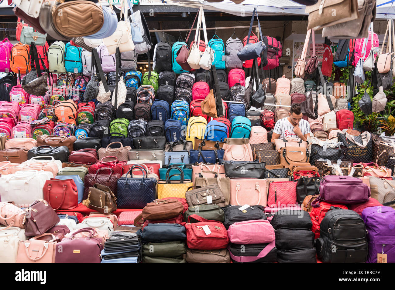 Stallholder surrounded by bags and luggage, apparently made by well known brands, at the Saturday market, aka Berivan Market, Selcuk, Turkey. - Stock Image