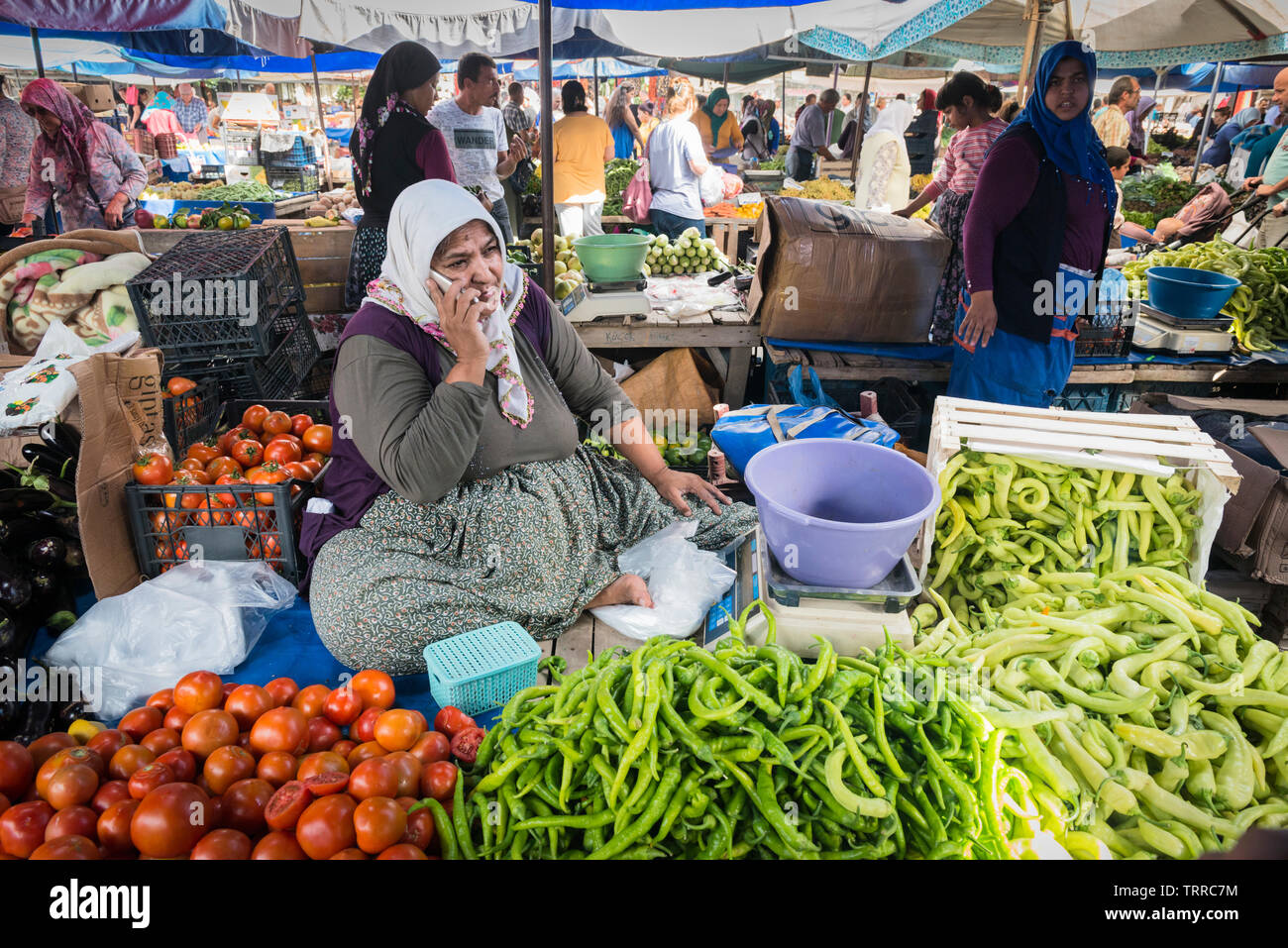 A stallholder selling vegetables chats on her mobile phone during the Saturday market, also known as Berivan Market, Selcuk, Turkey Stock Photo