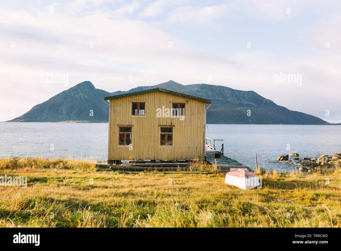 An old decaying wooden yellow house on the coast of Kvaløya island in northern Norway. In the front yard is a small boat. - Stock Image