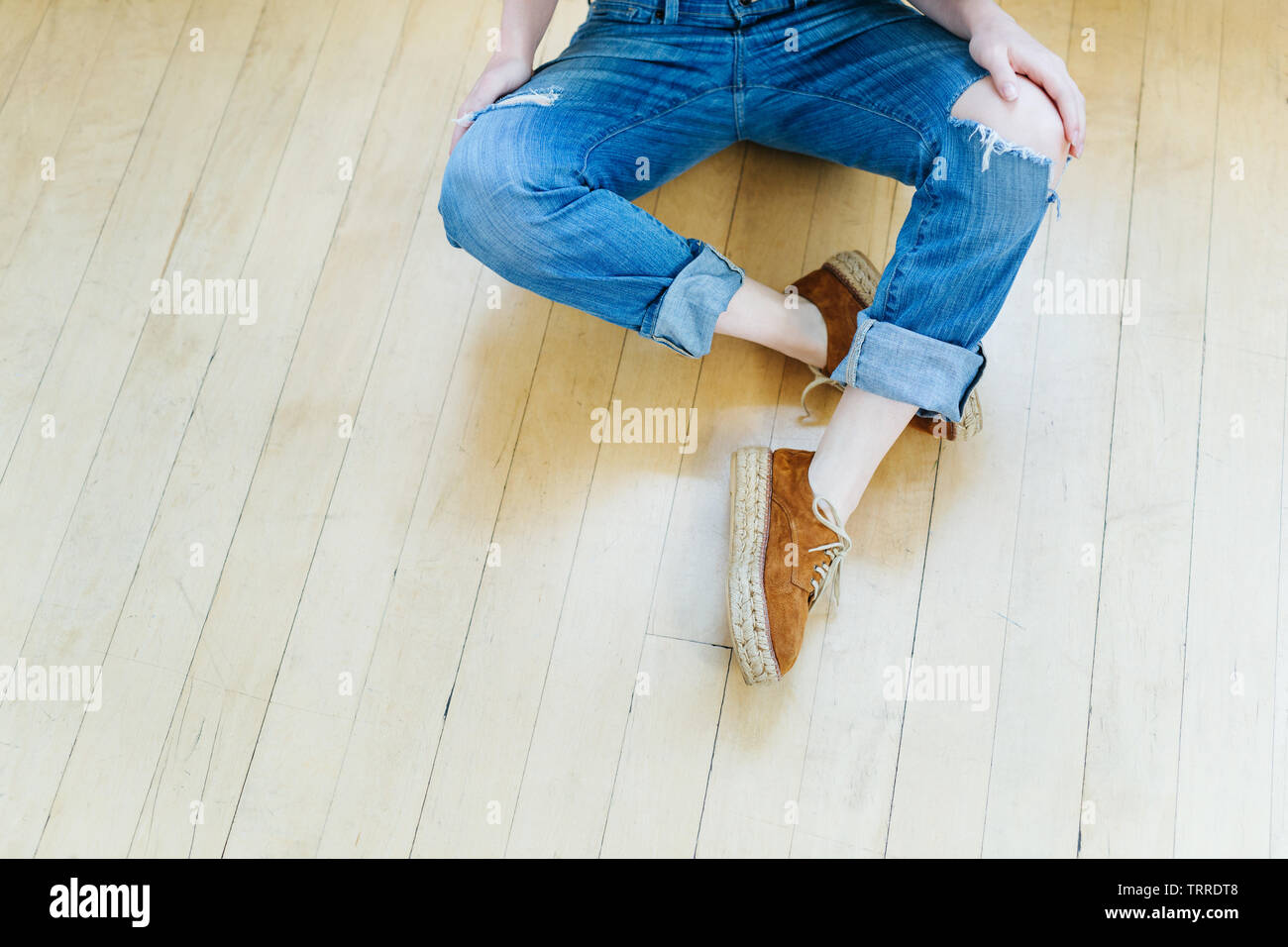 Young thin woman, wearing torn cuffed blue jeans and brown lace up suede and jute shoes, relaxes on wood floor with legs crossed and hands on knees - Stock Image