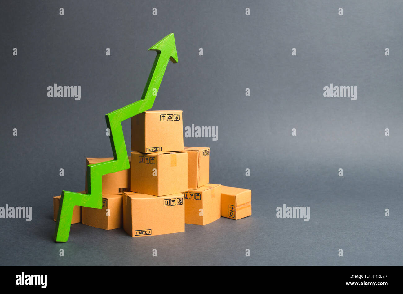 A pile of cardboard boxes and a green up arrow. The growth rate of production of goods and products, increasing economic indicators. Increasing consum - Stock Image