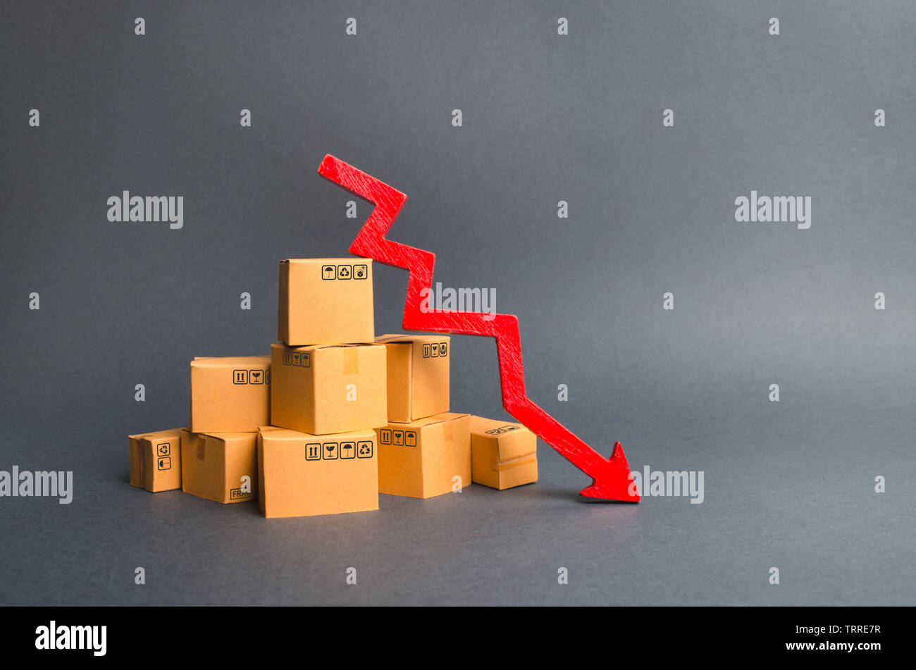 A pile of cardboard boxes and a red arrow down. The decline in the production of goods and products, the economic downturn and recession. Falling cons - Stock Image