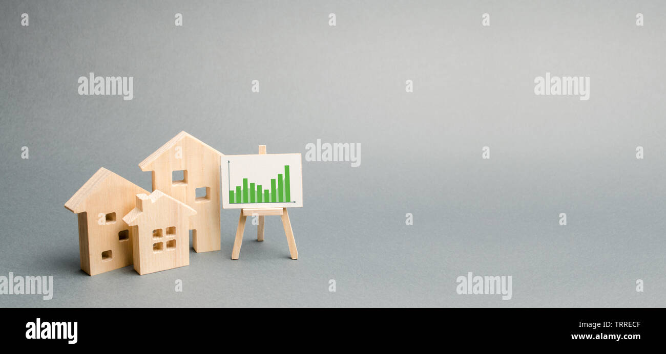 Wooden houses with a stand of graphics and information. Growing demand for housing and real estate. growth of the city and its population. Investments Stock Photo