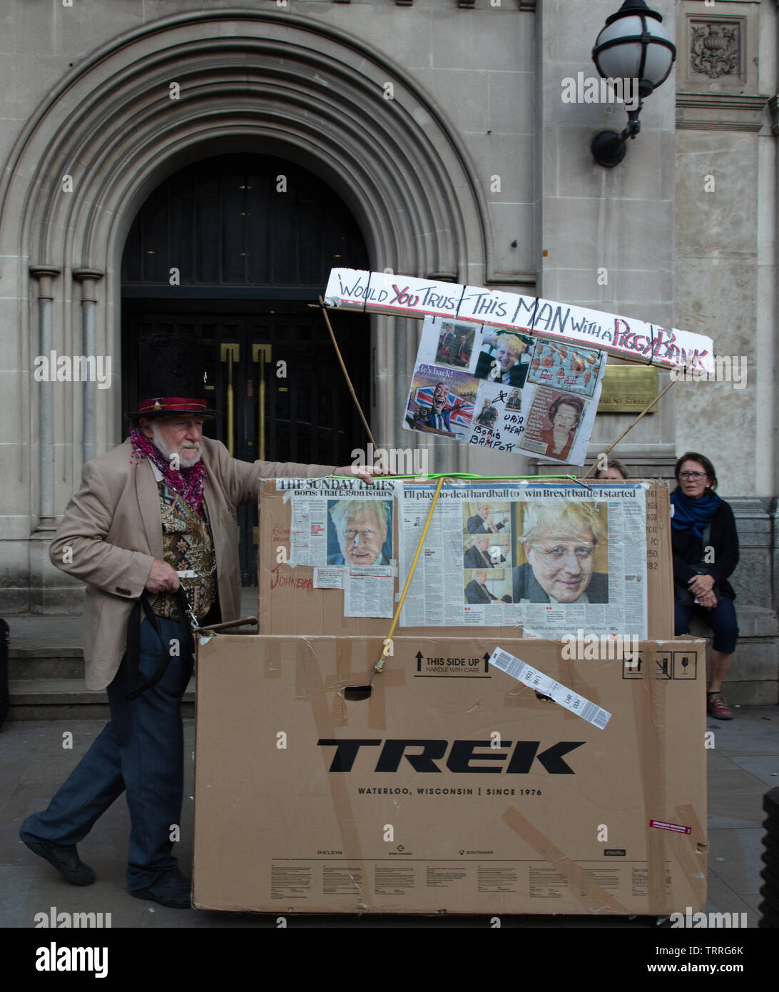 London, UK. 11th June 2019. Protester on no 1 Parliament Street, London, UK, with a collage of newspaper articles depicting Boris Johnson, once of the candidates for the job of Prime Minister of the UK, asking the question 'would you trust this man with a piggy bank'. Credit: Joe Kuis / Alamy News Stock Photo