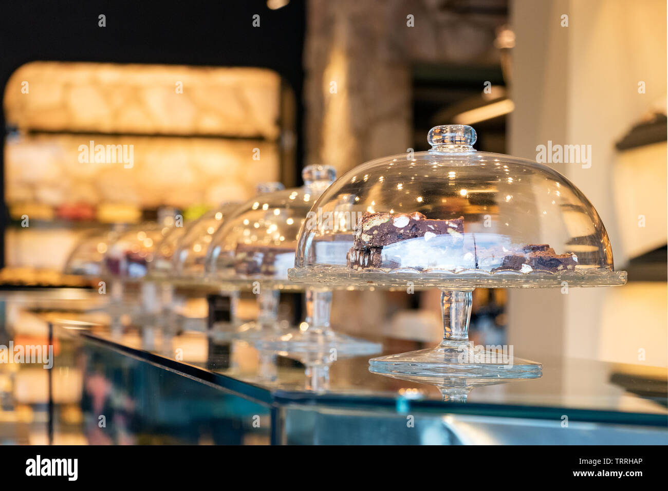 Pastry glass bells in a row placed on the counter inside a bakery store. - Stock Image