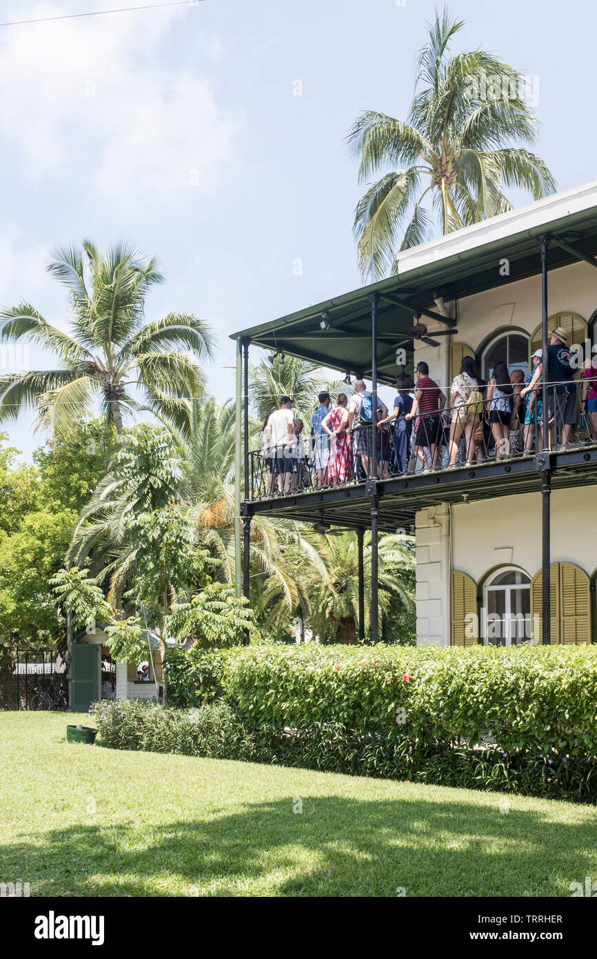 A view of visitors and tourists from around the world crowding the second floor balcony at the Ernest Hemingway House and Museum in Key West, Florida, USA Stock Photo