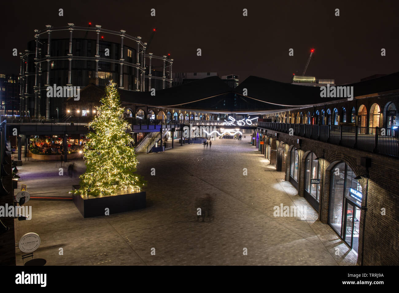 London, England, UK - December 14, 2018: People walk past Christmas decorations at the Coal Drops shopping centre in London's King's Cross regeneratio Stock Photo