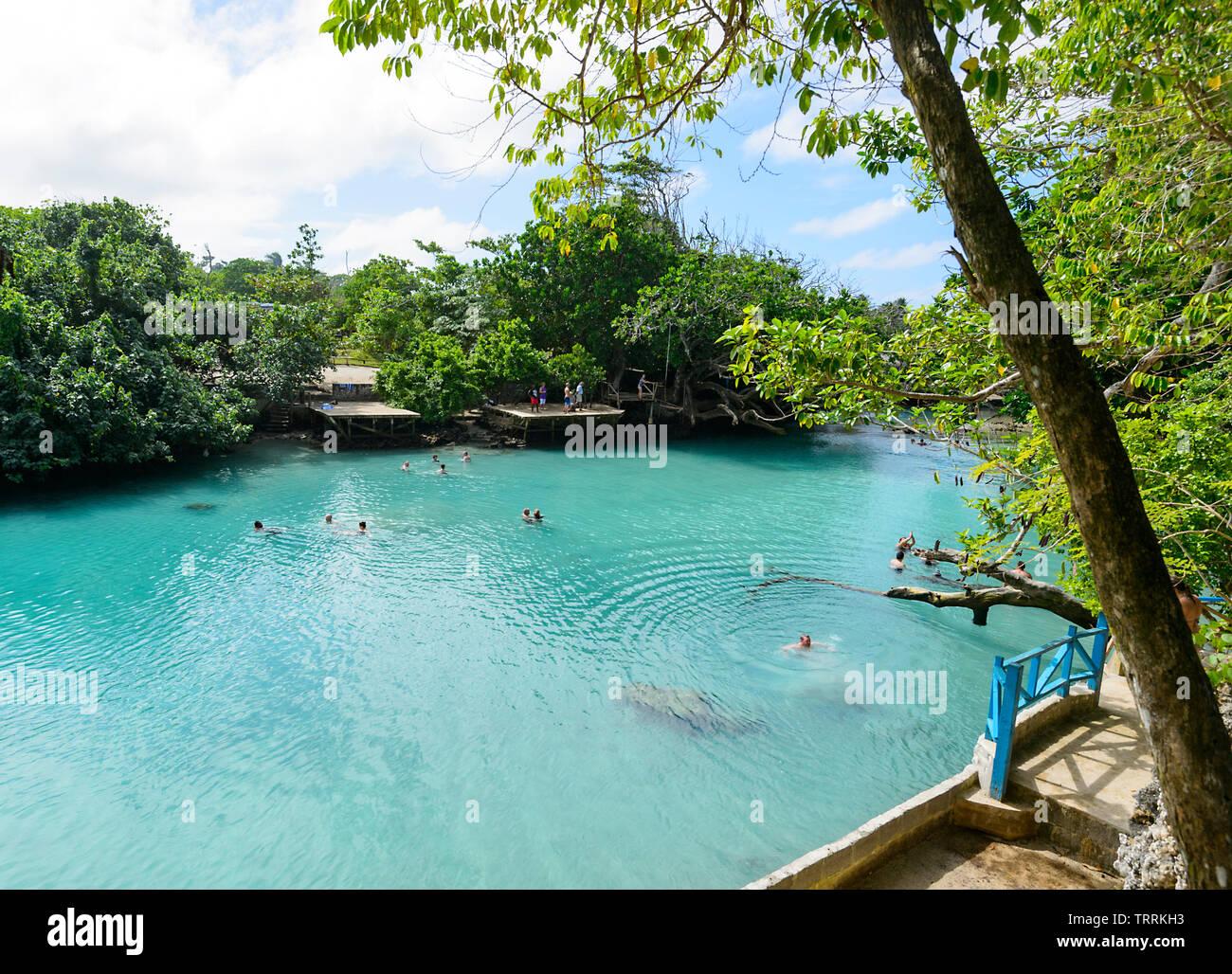 People swimming in Blue Lagoon, a popular scenic turquoise swimming hole near Port Vila, Efate Island, Vanuatu, Melanesia Stock Photo