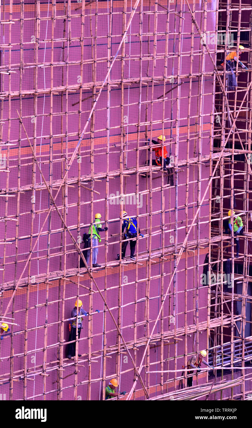 Workers at work on the scaffolding frame covering the outside wall of a building - Stock Image
