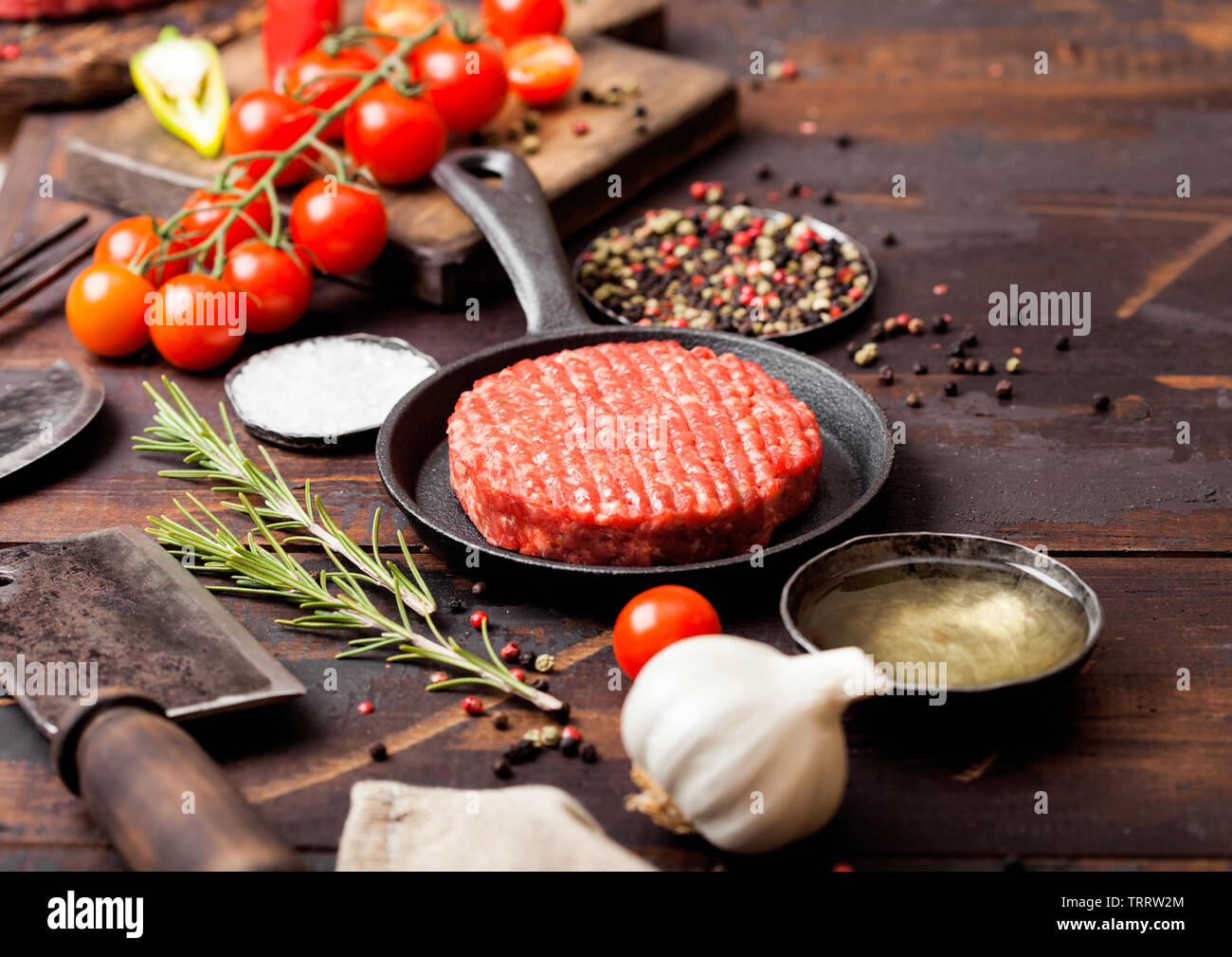 Fresh raw minced homemade farmers grill beef burger in frying pan with spices and herbs and meat hatchet on wooden board. Stock Photo