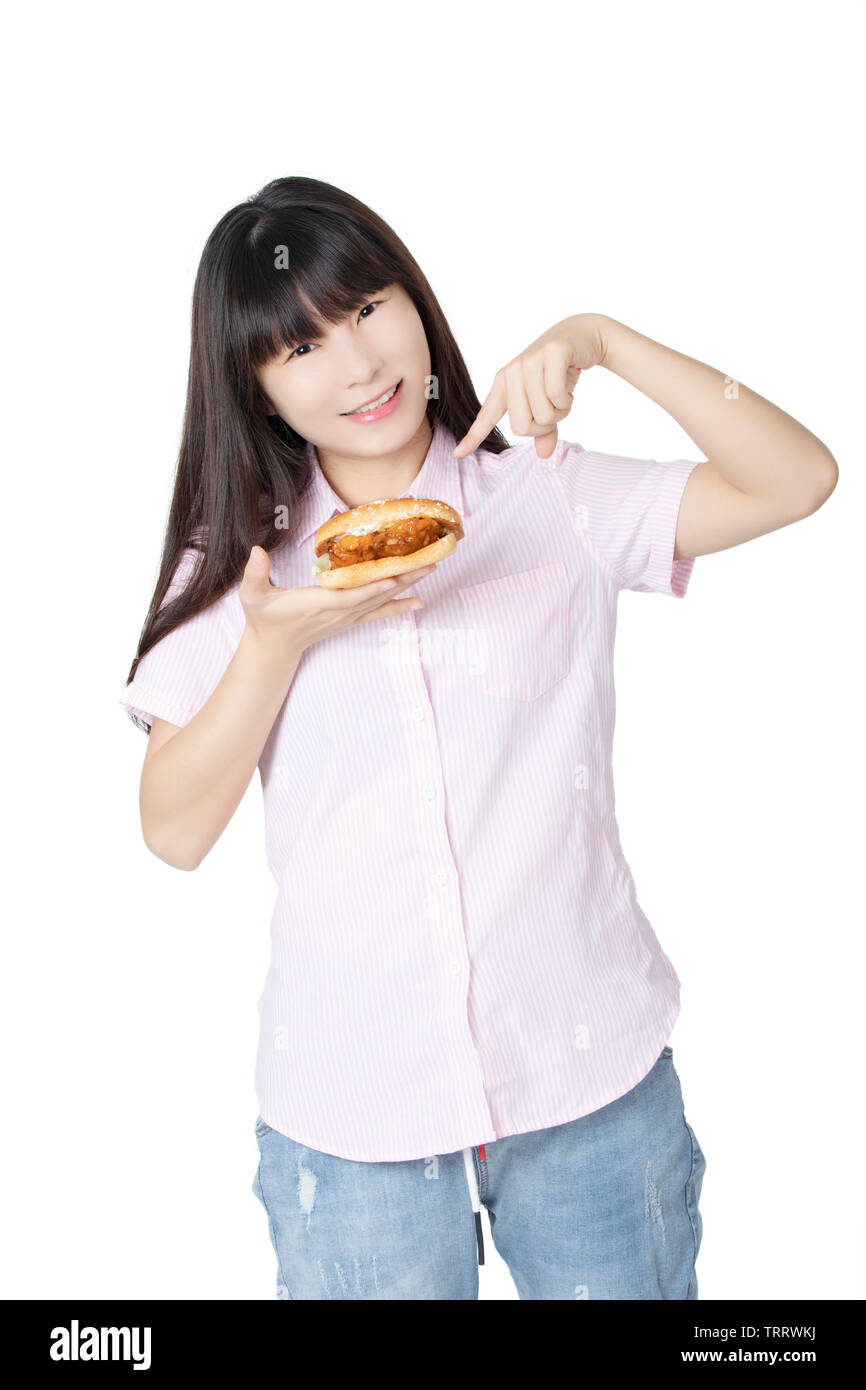 Beautiful Chinese American woman eating a Chicken Sandwich isolated on a white background - Stock Image