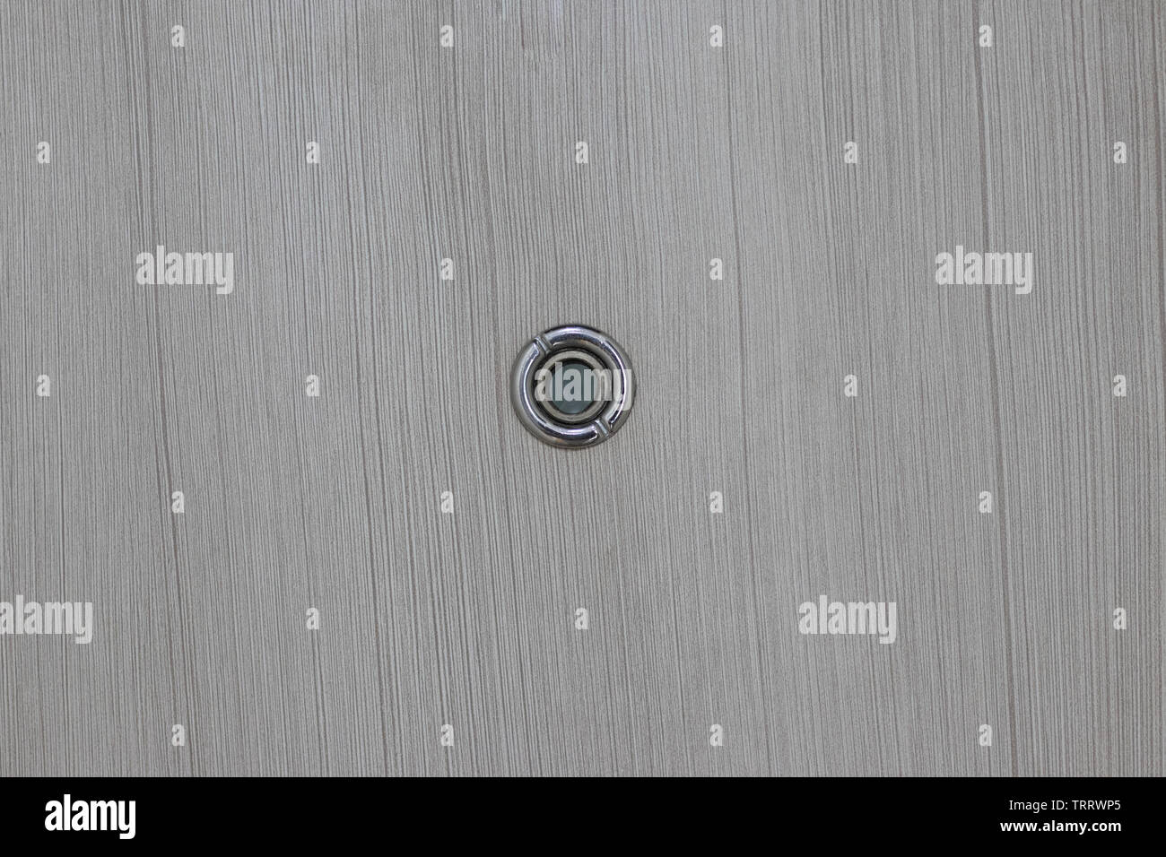 Close up door lens peephole on white wooden texture. - Stock Image