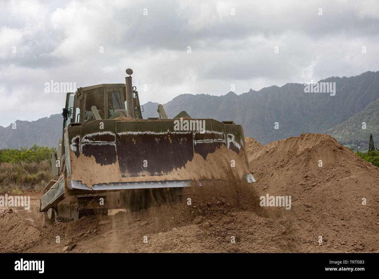 A U.S. Marine Medium Tractor Crawler assigned to Support Division, Marine Wing Support Detachment (MWSD) 24, excavates a training area, Marine Corps Training Area Bellows, June 6, 2019. Combat engineers created an anti-tank ditch and berm utilizing heavy earth movers, while the unit also completed scenarios for tactical convoy movements with simulated Improvised Explosive Devices and role players. This training assists MWSD-24 to sustain operational readiness when operating overseas. (U.S. Marine Corps photo by Sgt. Jesus Sepulveda Torres) - Stock Image
