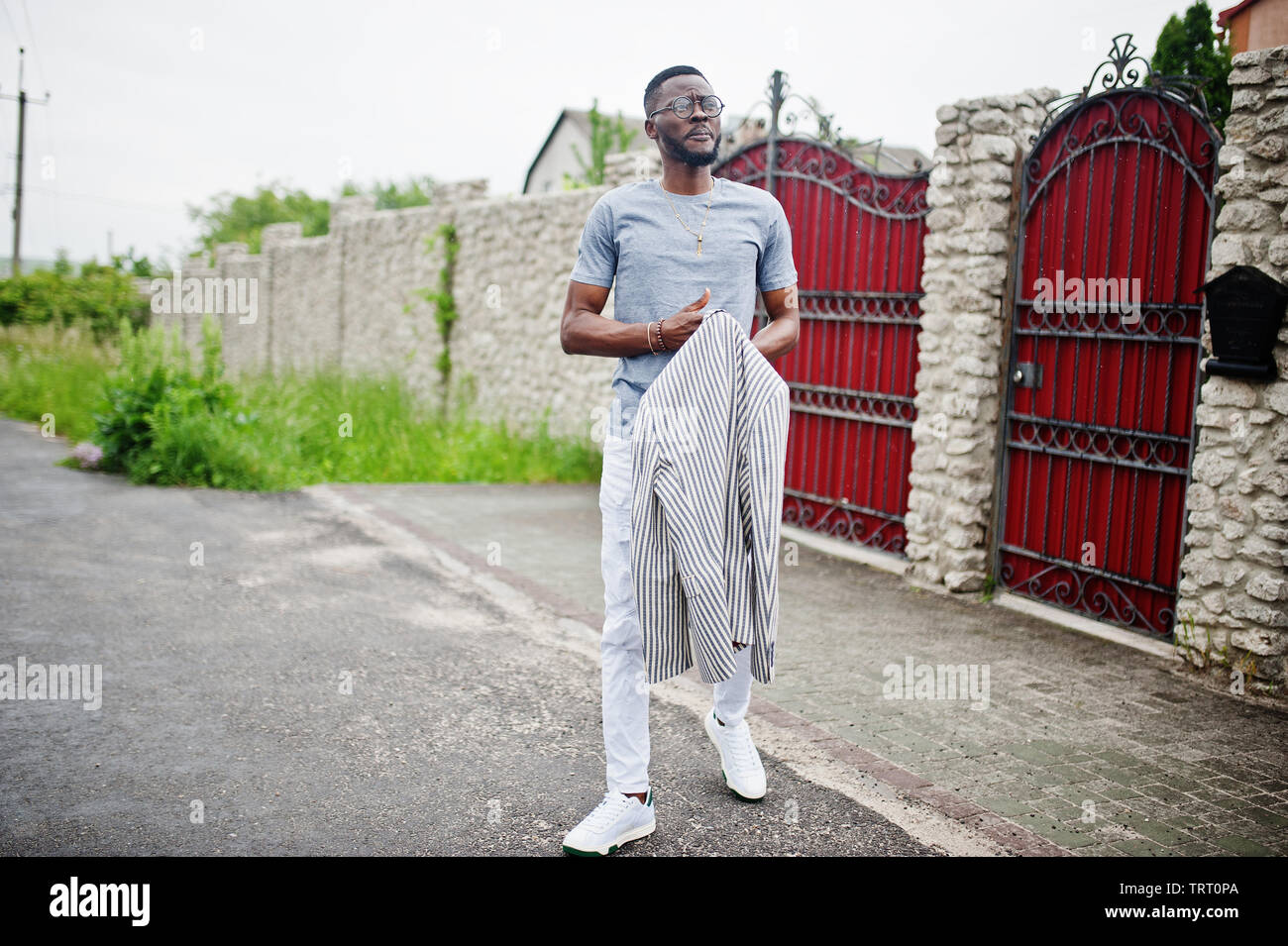 Rich and stylish african american man in blazer and eyeglasses outdoor against red fence. Stock Photo