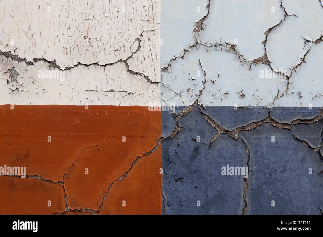 Four Rectangles Of Different Coloured Peeling Paints On An Old Cracked Shop Front In London's East End - Stock Image