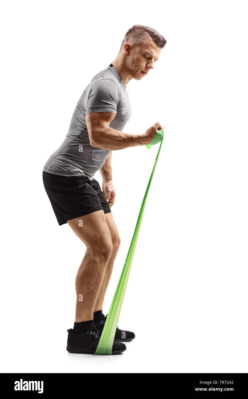 Full length profile shot of a young muscular guy exercising with an elastic band isolated on white background - Stock Image