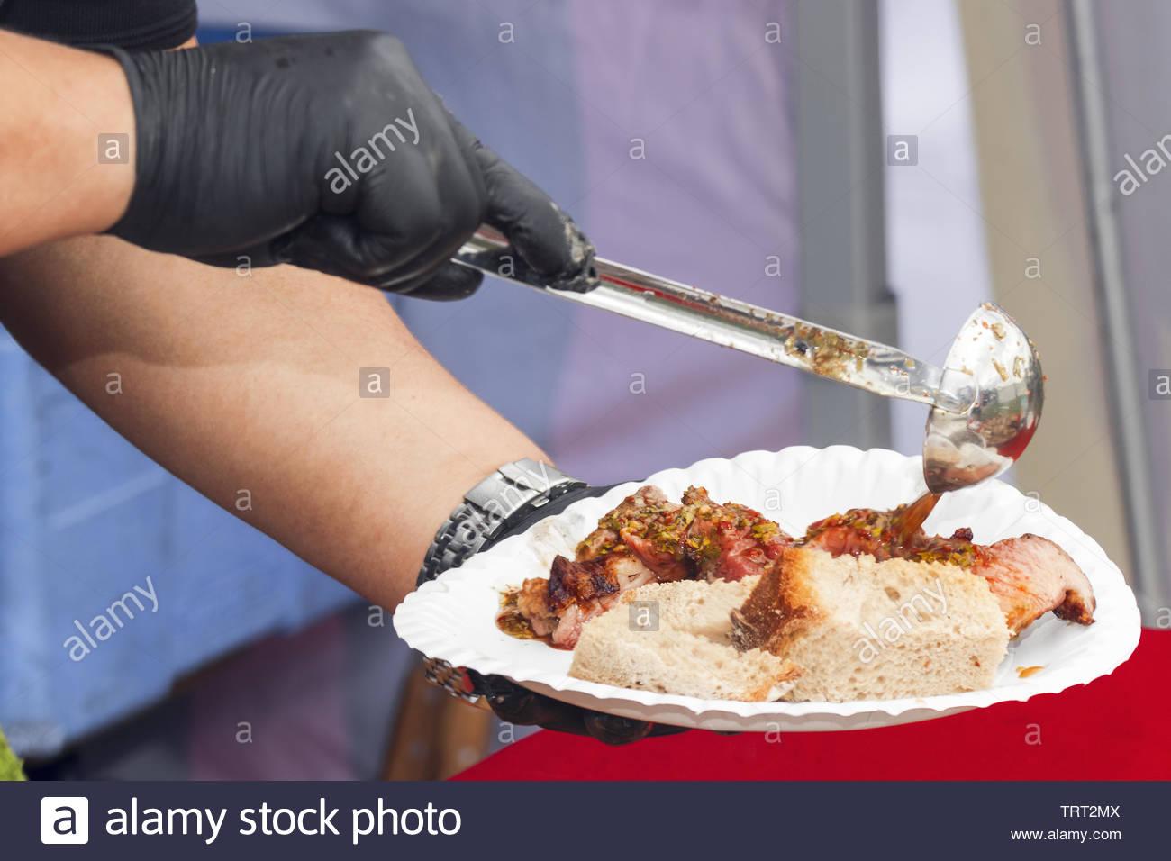 Chef  prepares rump steak with chimichurri sauce for visitors - Stock Image