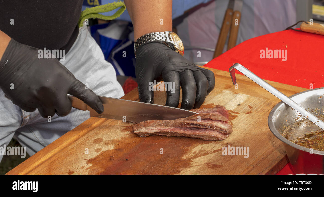Chef cuts grilled beef and prepares rump steak with chimichurri sauce for visitors - Stock Image