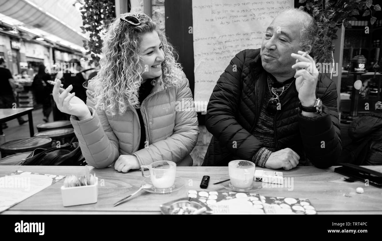 Smiling smoking couple in black and white looking at each other, Jerusalem, Israel. - Stock Image