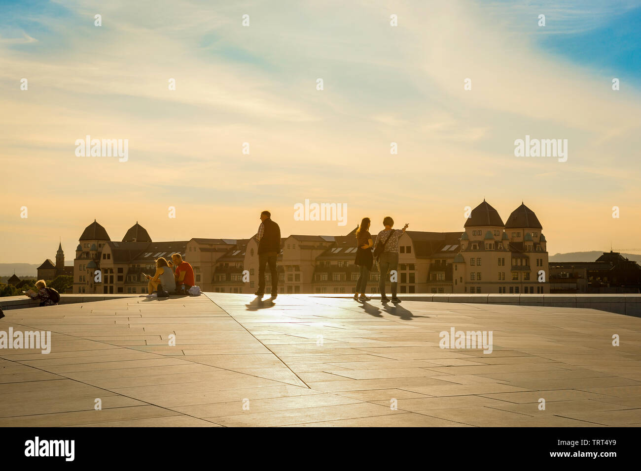Oslo Opera House, view on a summer evening of tourists on the roof of the Oslo Opera House (Operahuset) looking across the city, Norway. Stock Photo