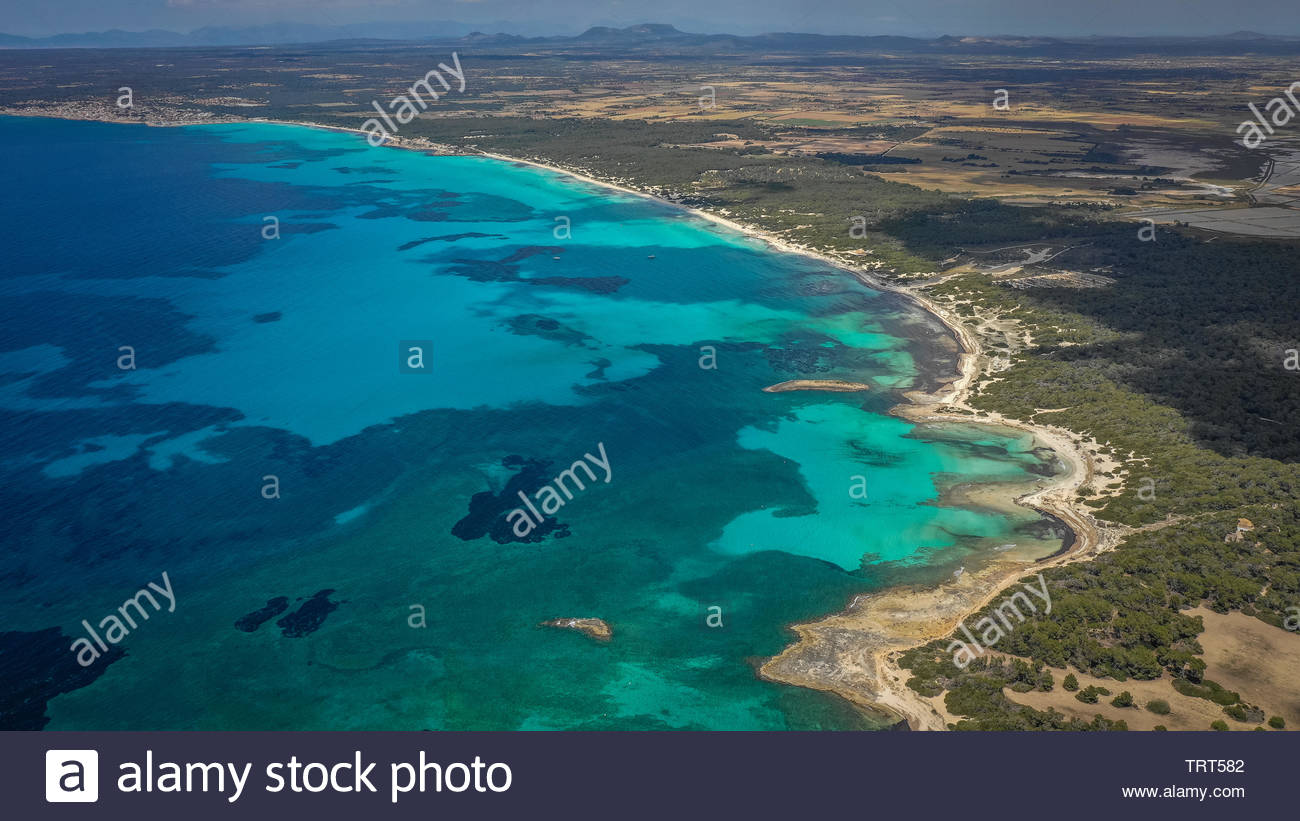 Landscape horizontal view of different shades of water next to green untouched natural land. Mountains in distance. - Stock Image
