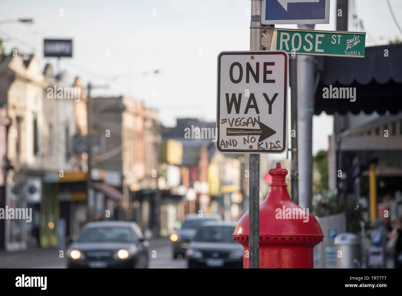 A One Way traffic sign with added words Vegan and no kids on Brunswick Street, Fitzroy in Melbourne, Victoria, Australia - Stock Image