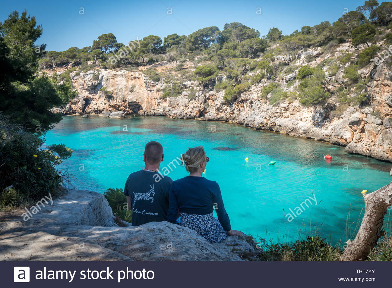 Young couple enjoying an idyllic vacation sitting overlooking a clear blue sheltered inlet between rocky cliffs on a sunny summer day Stock Photo