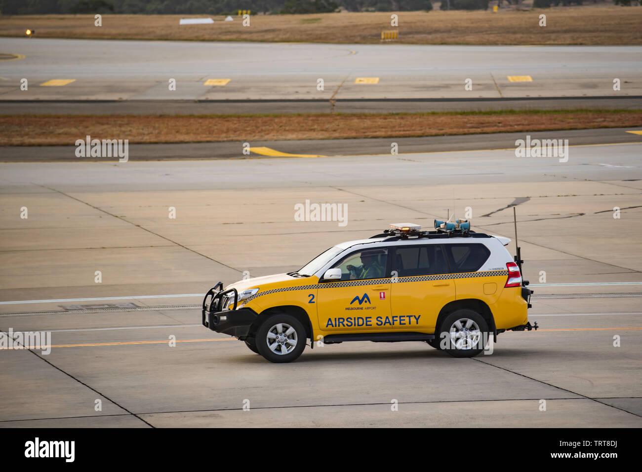 An airside safety vehicle driving near a runway at Melbourne's mainTullamarine airport in Victoria, Australia - Stock Image