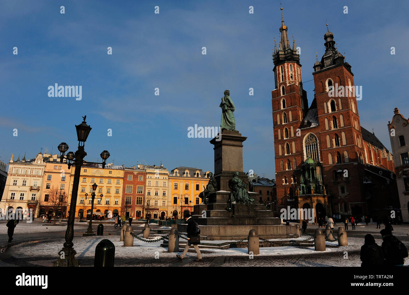 Poland. Krakow. Main Market Square. Adam Mickiewicz Monument in front of the St. Mary's Basilica, built in 14th century in Brick Gothic architecture style. - Stock Image