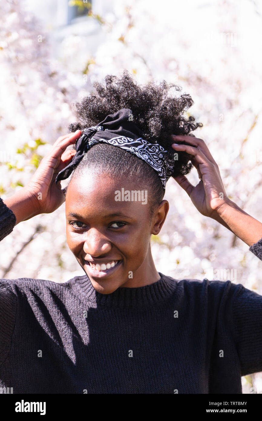 Close up portrait of smiling young attractive african american woman with hairstyle on background of blossom flowers Stock Photo