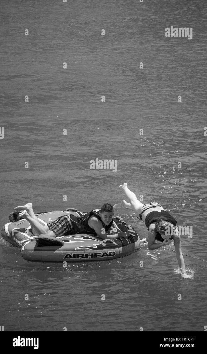 Young woman about to jump off from floating tube to the calm water in a hot Summer day. - Stock Image