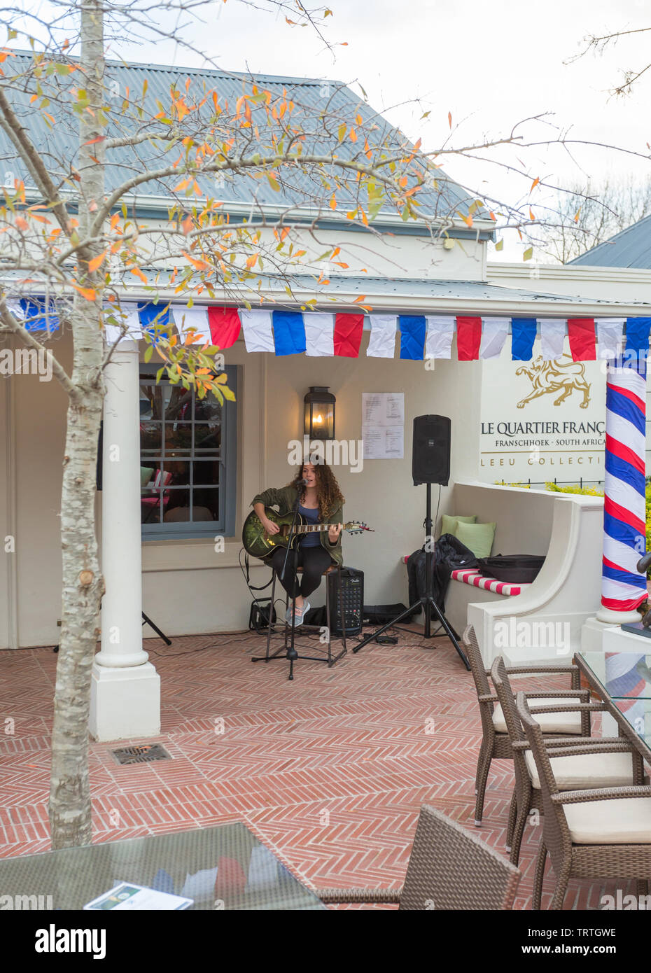 female singer and musician playing a guitar in a courtyard of a pub on Bastille day in Franschhoek, Cape Winelands, South Africa - Stock Image