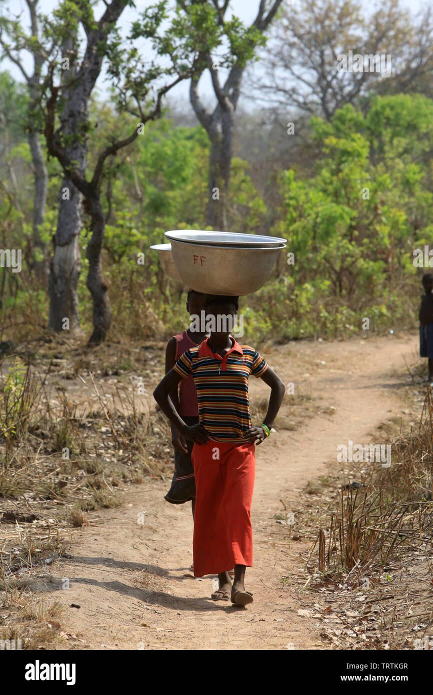 Africans girls get water with a bucket. Datcha Attikpayé. Togo. Afrique de l'Ouest. Stock Photo