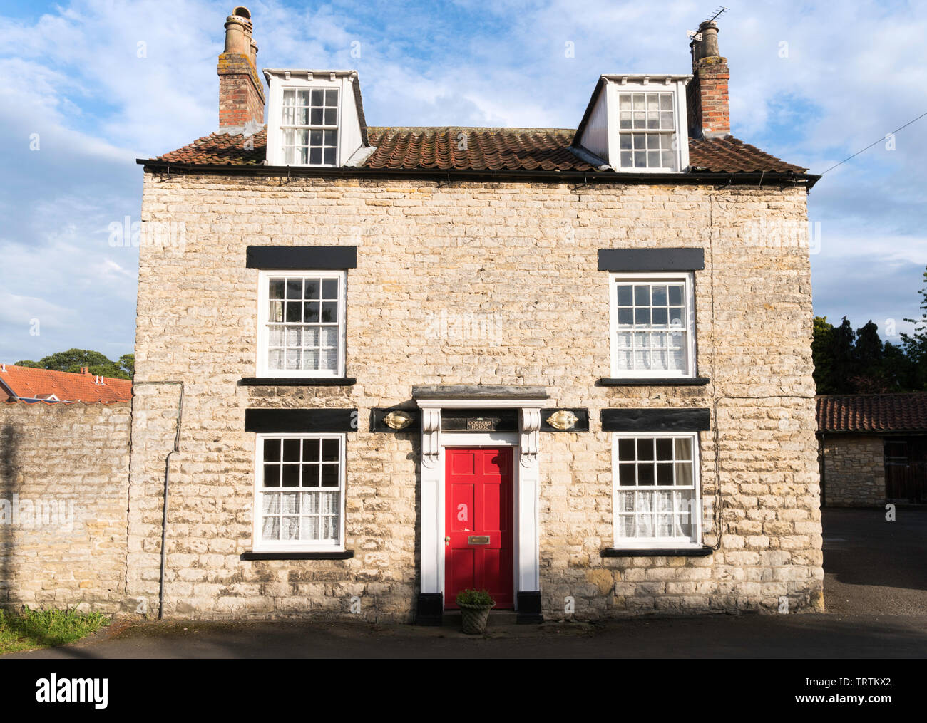 A grade II listed detached stone house, Dossers House, on The Green  in Slingsby, North Yorkshire, England, UK - Stock Image