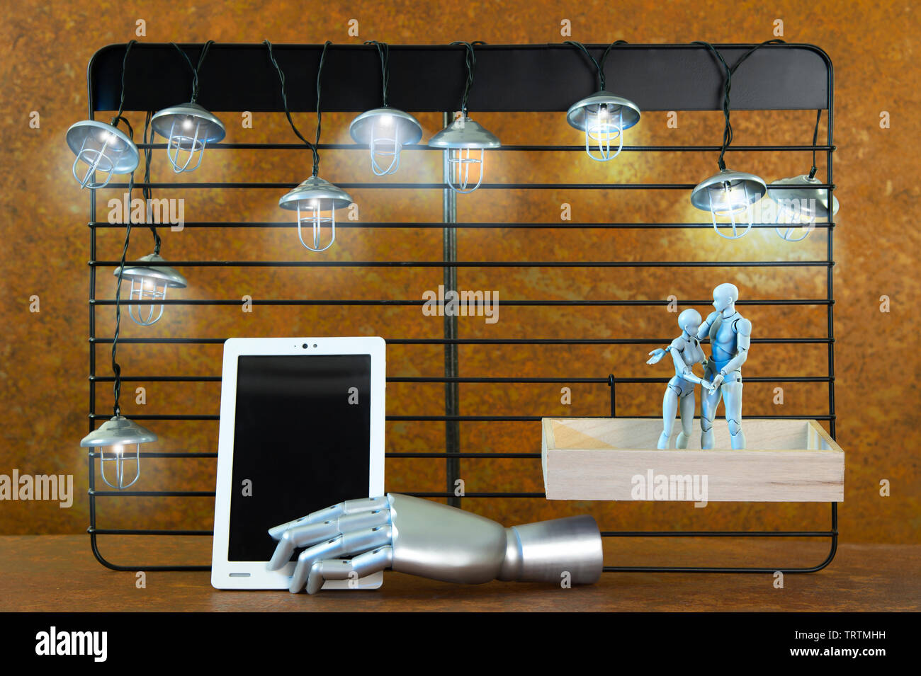 A black shelf in front of real rust. Mine lights shine. Two robot figures hugging each other. The man points to a tablet. A free space on a tablet lea Stock Photo